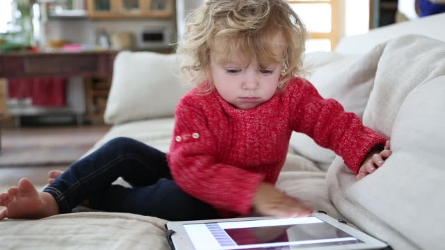 vidéos et rushes de 14 month old toddler boy playing with a digital tablet computer - tout petit