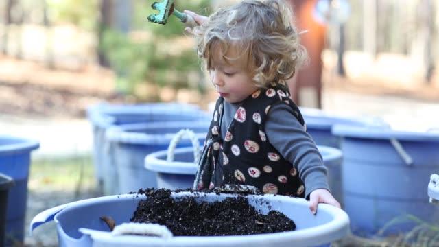 14 month old toddler boy playing with bins of soil - ein männliches baby allein stock-videos und b-roll-filmmaterial