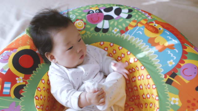 6 monate babymädchen spielen im spiel nest - 6 11 monate stock-videos und b-roll-filmmaterial
