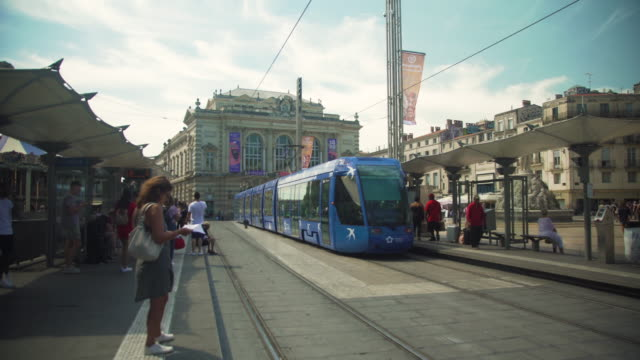 montpellier iconic image at comedie square with multi colored tramway - cable car stock videos & royalty-free footage