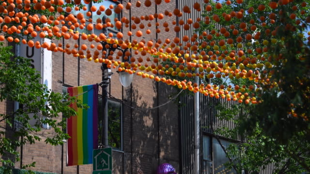 montreal, canada: gay village or simply the village rainbow coloured plastic balls decoration and flag in the famous neighbourhood which is a tourist attraction - montréal stock-videos und b-roll-filmmaterial