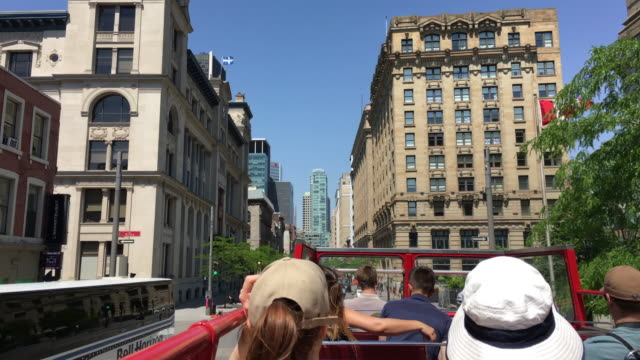 stockvideo's en b-roll-footage met montreal, canada: tour bus and tourist point of view while sightseeing the famous city and tourist attraction rich in valuable historic architecture - dubbeldekker bus