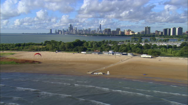 low aerial, montrose-wilson beach with city skyline in distance, chicago, illinois, usa - lago michigan video stock e b–roll