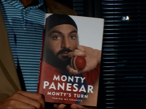 stockvideo's en b-roll-footage met monty panesar interview panesar posing for photocall with copy of his autobiography - autobiografie