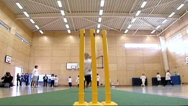 Monty Panesar playing cricket with children / interview ENGLAND London INT General views of group of schoolchildren playing cricket in sports hall...