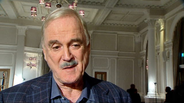 monty python reunion; john cleese interview sot - had my hips replaced in 1999, my knee replaced in 2006 so i can't even do a geriatric version of... - モンティ・パイソン点の映像素材/bロール
