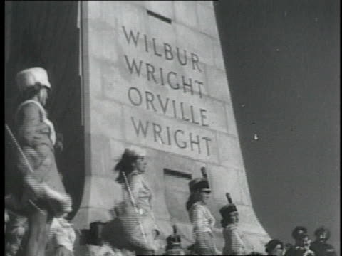 vídeos y material grabado en eventos de stock de monument at kitty hawk dedicated to the wright brothers / painting of wilbur and orville wright / biplane flying in the sky - 1952