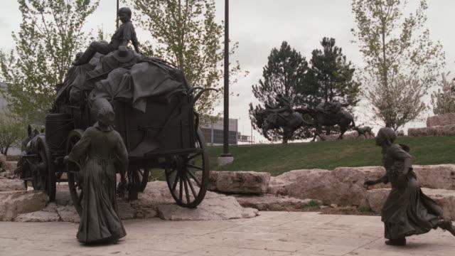 vídeos de stock, filmes e b-roll de a monument in omaha, nebraska features a sculpture of pioneers traveling with their heavily laden wagon. - figura feminina