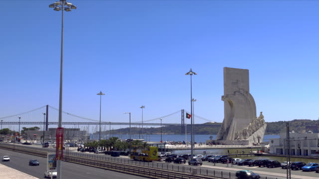 monument to the discoveries or padr‹o dos descobrimentos with the 25 de abril bridge and the tejo in the background. - 4月25日橋点の映像素材/bロール
