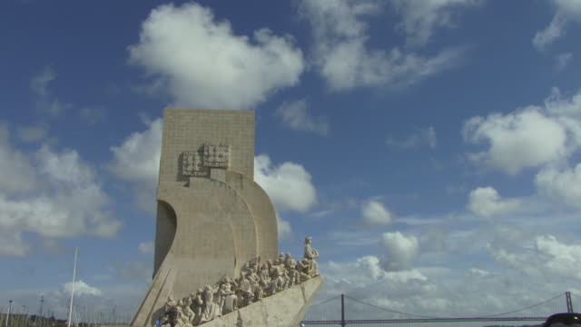 ws monument to the discoveries with april 25th bridge in background / lisbon, portugal - 4月25日橋点の映像素材/bロール