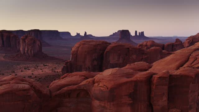 monument valley at sunset from behind rocky outcrop - butte rocky outcrop stock videos & royalty-free footage