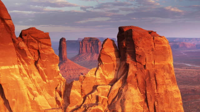 monument valley buttes in red sunset light - drone shot - rock formation stock videos & royalty-free footage