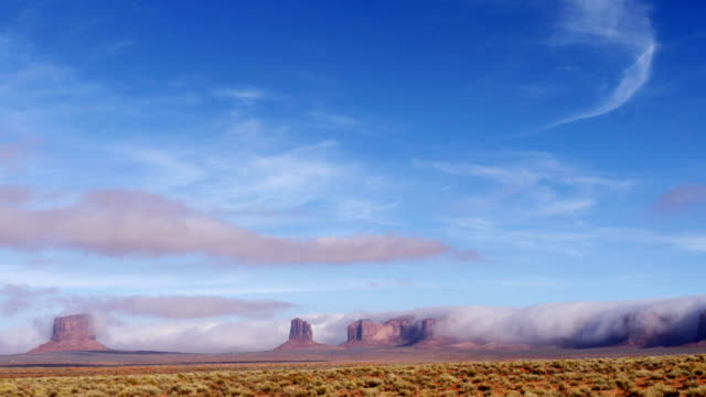 monument valley wrapped in clouds - stratus stock videos & royalty-free footage