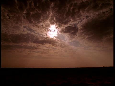 wa moody sky over dark landscape, white sun hiding behind clouds, gujarat, india - 幻想点の映像素材/bロール