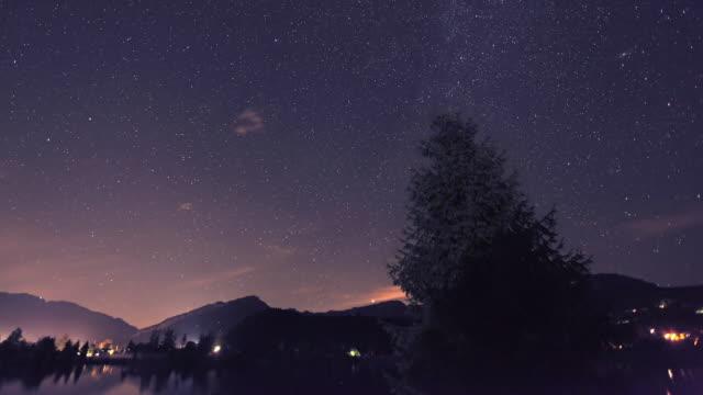t/l ws moody sky over lake and mountains at night / steeg, tyrol, austria - 流星点の映像素材/bロール