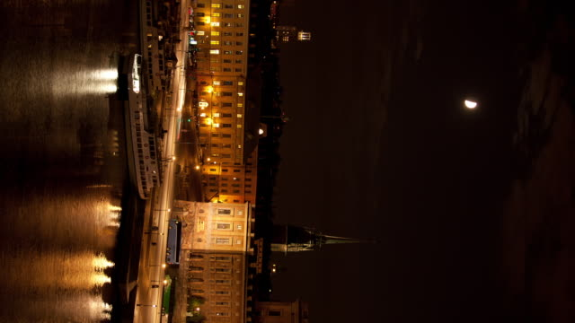 Moon passes over German church and traffic in Gamla Stan