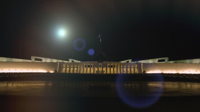 moon rises behind parliament house, australia - parlamentsgebäude regierungsgebäude stock-videos und b-roll-filmmaterial