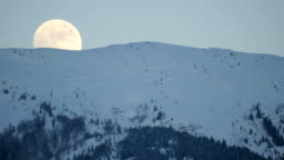 Moon rising above a mountain during winter