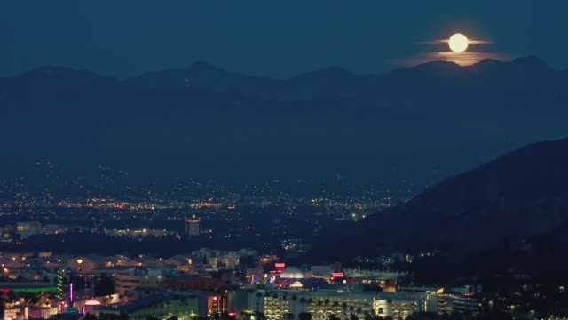 T/L HA WS Moon rising above San Gabriel Mountains and traffic in Universal Studios cityscape at night / Universal City, California, USA