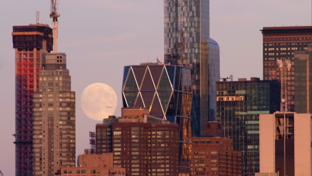 Moon rising behind One57 residential building against a clear sky. Airplanes fly in front of moon.