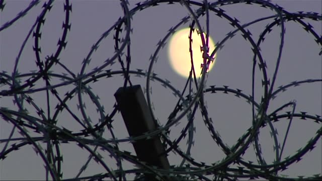 vídeos de stock, filmes e b-roll de moon seen through prison fence - prisoner