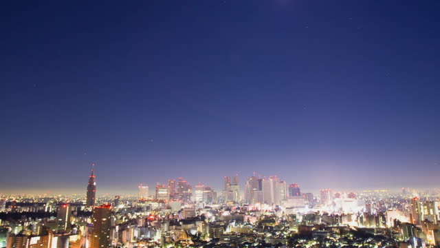WS T/L Moon sets as sun rises over Shinjuku business, shopping and entertainment district / Tokyo, Japan