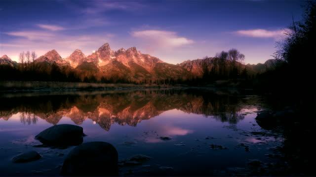 Moon setting over mountain range at dawn