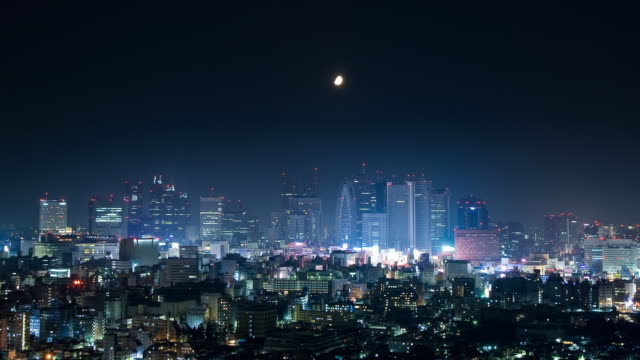 t/l ws ls ha moon setting over shinjuku, tokyo, japan - distant stock videos and b-roll footage