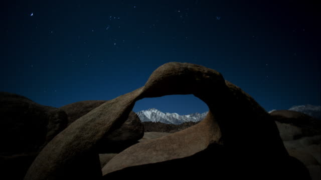 vídeos de stock, filmes e b-roll de moonlight illuminates mobius arch in the alabama hills of california's eastern sierra. - chuva de meteoros