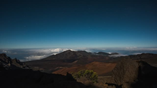 a moonlight shadow creeps across the surface of a dormant volcano as clouds swirl and stars rise at night on haleakala - kegel stock-videos und b-roll-filmmaterial
