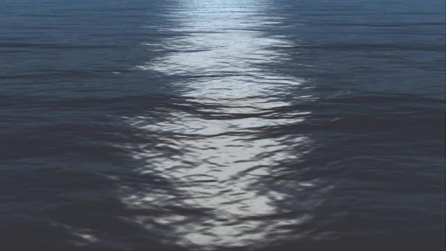 Moonlight shines down on ocean waters (Loop).