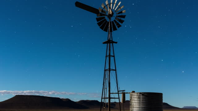 A moonlit Karoo farm landscape with windmill and an old metal well