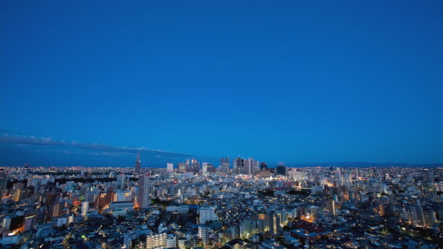 WS T/L Moonset and sunrise over the Shinjuku business, shopping and entertainment district / Tokyo, Japan