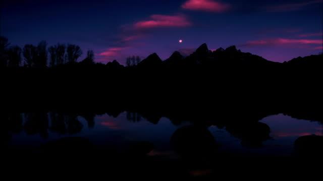 ws, pan moonset by lake in teton range, wyoming, usa - グランドティトン点の映像素材/bロール