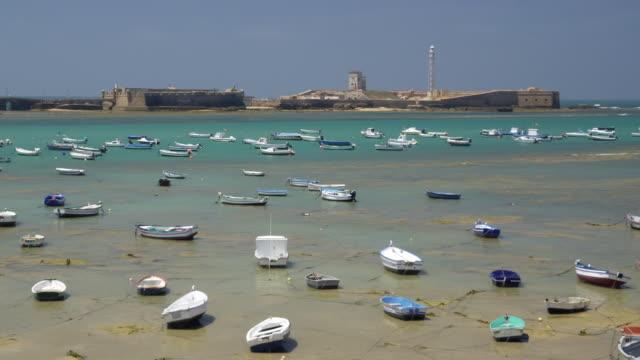 ws moored boats with castillo de san sebastian in background / cadiz, spain - 2k resolution stock videos and b-roll footage