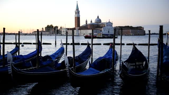 Moored gondolas and San Giorgio Maggiore church at sunrise. Venice, Italy.