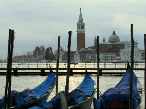 ws zo moored gondolas floating on grand canal as tour boats travel past church of san giorgio maggiore / venice, italy - ausflugsboot stock-videos und b-roll-filmmaterial