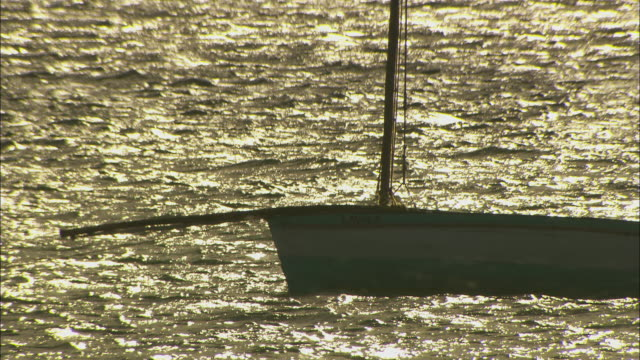 a moored yacht gently bobs on a body of water.  - ダウ船点の映像素材/bロール