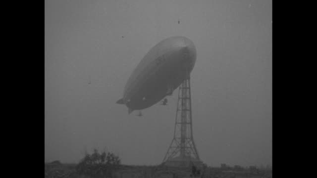 Mooring mast / VS footage of men attending to USS Shenandoah attached at top of mast with a closer view of damage