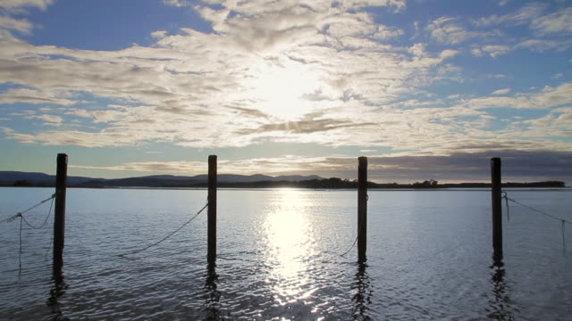 stockvideo's en b-roll-footage met ws t/l mooring posts stand like sentinels against clouds at mallacoota estuary / mallacoota, victoria, australia - houten paal