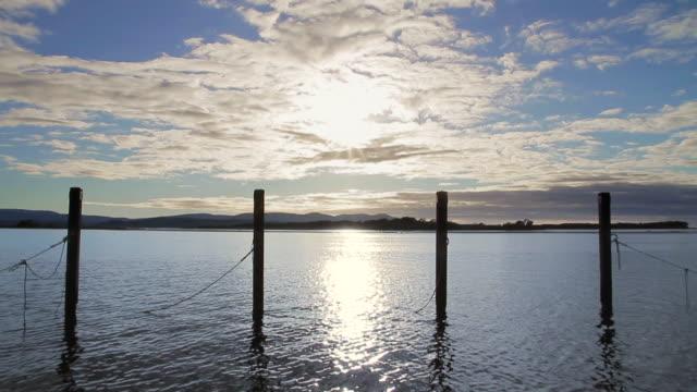 WS T/L Mooring posts stand like sentinels against clouds at Mallacoota Estuary / Mallacoota, Victoria, Australia