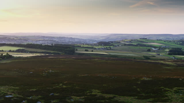 moorland and fields in pennines with keighley in distance - aerial view - pennines stock videos and b-roll footage
