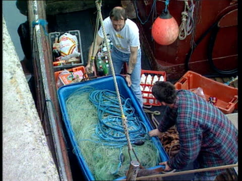 more anglo-spanish clashes; england cornwall newlyn cms skipper, mick faulkner, on quay sorting out nets tilt down hake net int tms crate of fish... - ペンザンス点の映像素材/bロール