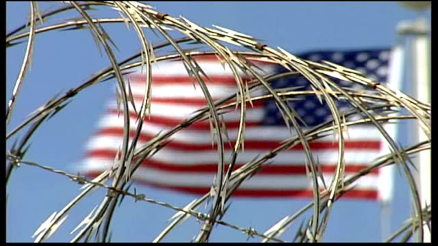 more details emerge on shooting of osama bin laden file guantanamo bay ext us flag flying against barbed wire fence anonymous shot of detainee... - waterboarding stock videos & royalty-free footage