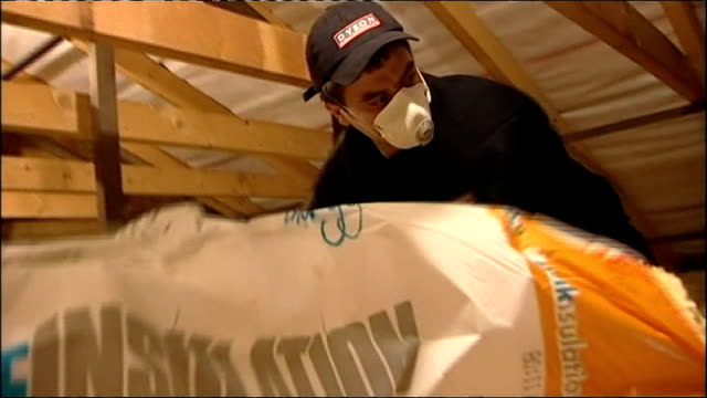 300000 more families could fall into fuel poverty by christmas various of people laying insulation in domestic lofts - isoliermaterial stock-videos und b-roll-filmmaterial