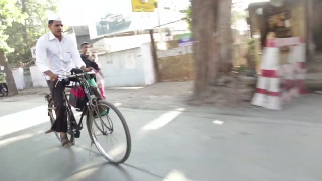 More footage of Dabbawallas eating and delivering packages in Mumbai India on December 12 2015 Shots women cook food for Dabbawallas Dabbawalla...