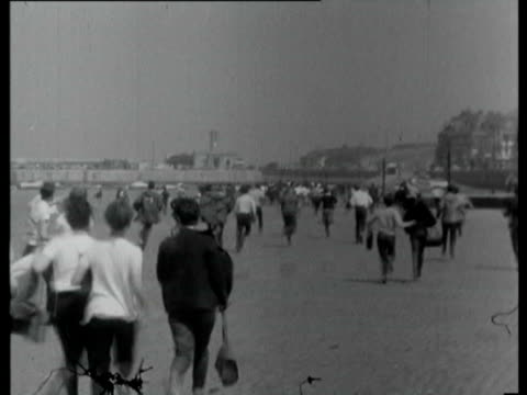 stockvideo's en b-roll-footage met more shots of young people running off beach: police making arrests and moving people on. / united kingdom - 1965