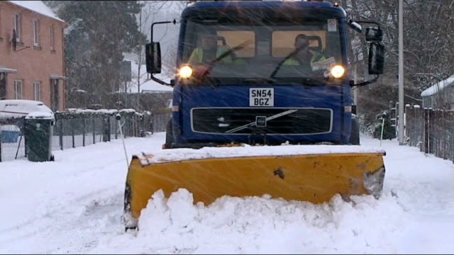 people along snowcovered road snow plough towards clearing snow from road school sign with snow falling door of closed school 'heavy snow forecast... - snow vehicle stock videos and b-roll footage