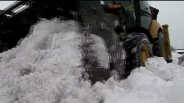 more snow falls across the uk lib / t23031310 low angle shot of snow plough towards and past clearing snow from road person using shovel to clear... - itv weekend lunchtime news点の映像素材/bロール
