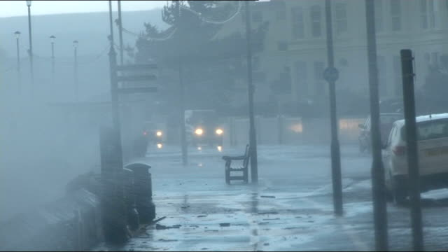 more stormy conditions and heavy rain in england and wales; devon: waves breaking against sea wall waves breaking over sea front road waves crashing... - in front of点の映像素材/bロール